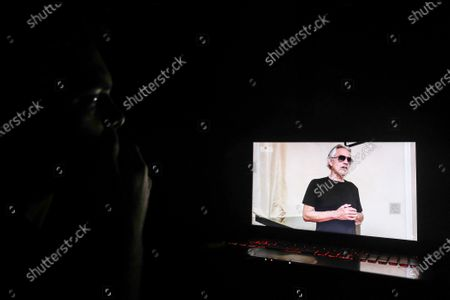 A man smokes a cigarette while watching Italian singer Andrea Angel Bocelli performing during the 'One World: Together At Home' broadcast at his home in Paris, France, 18 April 2020. The eight-hour event run by the Global Citizen movement in cooperation with US artist Lady Gaga and the World Health Organization (WHO) is being live-streamed and broadcast on TV to support the health workers around the world fight with the SARS-CoV-2 coronavirus pandemic which causes the Covid-19 disease.