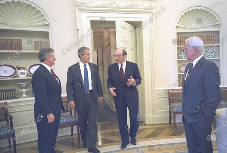 United States President George W. Bush talks to Federal Reserve Board Chairman Alan Greenspan, Treasury Secretary Paul O'Neill and White House Chief of Staff Andy Card in the Oval Office of the White House in Washington, DC, after their lunch meeting. Mandatory