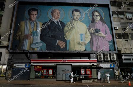 Stock Image of City workers disinfect a bus stop to help prevent the spread of new coronavirus outside a closed cinema with a mural of film directors, from left, Federico Fellini, Alfred Hitchcock, Luis Buñuel and Lucrecia Martel in Montevideo, Uruguay