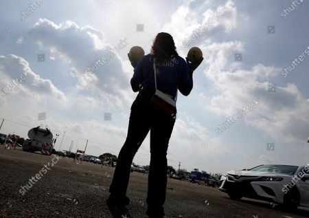 City worker Michelle Johnson holds up melons as cars drive by to collect bundles of food during a food distribution event, in Miami Gardens, Fla