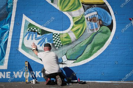 General view of artist Marty Lyons putting the finishing touches to a mural paying tribute to the NHS and key workers on the Falls Road in west Belfast, Northern Ireland.