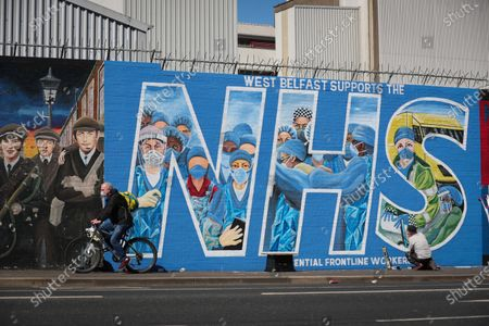 Stock Picture of General view of artist Marty Lyons putting the finishing touches to a mural paying tribute to the NHS and key workers on the Falls Road in west Belfast, Northern Ireland.