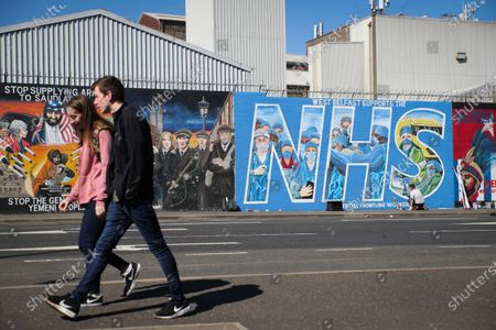 Stock Image of General view of artist Marty Lyons putting the finishing touches to a mural paying tribute to the NHS and key workers on the Falls Road in west Belfast, Northern Ireland.