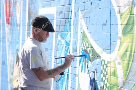 Stock Photo of General view of artist Marty Lyons putting the finishing touches to a mural paying tribute to the NHS and key workers on the Falls Road in west Belfast, Northern Ireland.