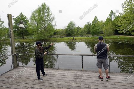 Susan Shin, left, catches a fish while fishing with her husband Chris, at Sheldon Lake State Park and Environmental Learning Center in Houston. Texas Gov. Greg Abbott has ordered state parks to reopen Monday after being closed due to the COVID-19 outbreak