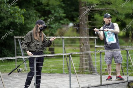 Susan Shin, left, catches a fish while fishing with her husband, Chris, at Sheldon Lake State Park and Environmental Learning Center in Houston. Texas Gov. Greg Abbott has ordered state parks to reopen Monday after being closed due to the COVID-19 outbreak
