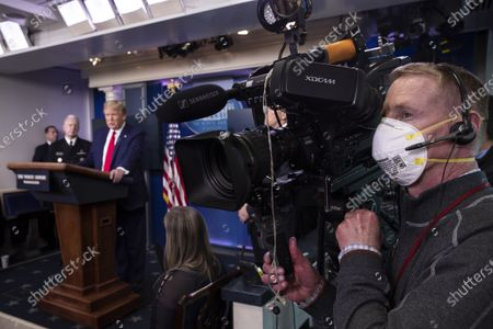 CNN's Peter Morris wears an N-95 mask while covering President Donald Trump as he speaks about the coronavirus in the James Brady Press Briefing Room of the White House, in Washington