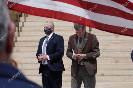 Wyoming Gov. Mark Gordon, right, with an unidentified bodyguard left, reads a prayer to protesters at the state Capitol in Cheyenne on . The crowd of about 100 people were protesting school and business shutdowns to limit the spread of the coronavirus