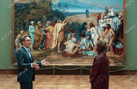 """Stock Picture of From the stream of the Okko OTT-platform, released, Russian musician Sergei Shnurov, left, and Tretyakov Gallery director Zelfira Tregulova talk during an online excursion at the empty Tretyakov Gallery, in front of """"The Appearance of Christ Before the People"""" artwork by Russian painter Alexander Ivanov, in Moscow, Russia. Russians from many walks of life are struggling to adapt to working remotely because of the coronavirus outbreak. The shutdown has driven many businesses to the verge of collapse and made millions jobless, according to estimates"""