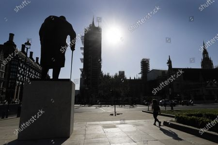The statue of Winston Churchill is silhouetted in front of Britain's Houses of Parliament as the country is in lockdown to help curb the spread of coronavirus, in London, . Britain's Parliament is going back to work, and the political authorities have a message for lawmakers: Stay away. U.K. legislators and most parliamentary staff were sent home in late March as part of a nationwide lockdown to slow the spread of the new coronavirus. With more than 16,500 people dead and criticism growing of the government's response to the pandemic, legislators are returning Tuesday - at least virtually - to grapple with the crisis