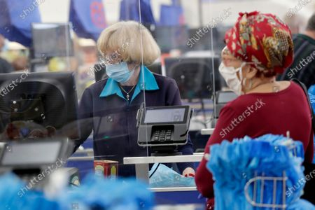 Cashier Nancy Alvarez wears a protective mask as she works behind a plastic shield at the Presidente Supermarket during the new coronavirus pandemic, in Hialeah, Fla. All employees are required to wear masks which are provided by the company