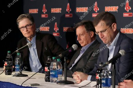 Boston Red Sox owner John Henry, chairman Tom Werner and CEO Sam Kennedy react during a news conference at Fenway Park in Boston. The Boston Red Sox were stripped of their second-round pick in this year's amateur draft by Major League Baseball for breaking video rules in 2018 and former manager Alex Cora was suspended through the 2020 postseason for his conduct as bench coach with the Houston Astros the previous year. Baseball Commissioner Rob Manfred announced his decision, concluding Red Sox replay system operator J.T. Watkins used in-game video to revise sign sequences provided to players