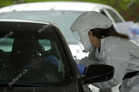 Truman Medical Center nurse Kelly Meyer takes a sample for a COVID-19 test during a drive-in testing outreach in the parking lot of a church in Kansas City, Mo. . The city continues to be under an extended stay-at-home order until May 15 in an attempt to slow the spread of the coronavirus
