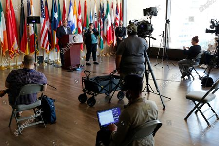 Members of the media observe social distancing as Dallas Mayor Eric Johnson, at podium, responds to a question during a news conference at City Hall where he discussed the latest developments amid the COVID-19 outbreak, in Dallas on