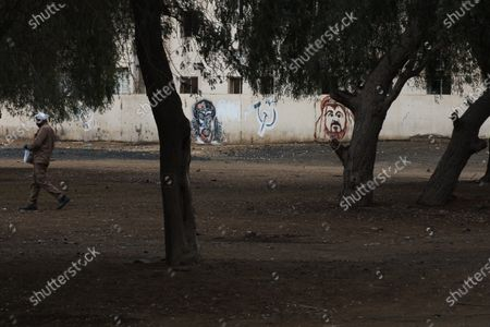 Graph, a laborer walks past graffiti showing Marxist icon Che Guevara, a hammer and sickle and a portrait of Dubai ruler Sheikh Mohammed bin Rashid Al Maktoum in the Al Quoz neighborhood of Dubai, United Arab Emirates. Migrant workers in oil-rich Gulf Arab states find themselves trapped by the coronavirus pandemic. They are losing jobs, running out of money and desperate to return home as the coronavirus, stalks their labor camps. An unknown number of workers have contracted the virus or have suddenly been forced into mass quarantines, leaving them exposed and painfully vulnerable with little recourse for help