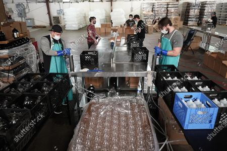 Workers fill bottles with hand sanitizer at the William Price Distilling Company, in Houston. The company, which started making hand sanitizer to help fight the coronavirus, is hiring out-of-work bartenders to help during the COVID-19 outbreak