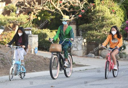 Stock Image of Laeticia Hallyday riding her bike with her children in Pacific Palisades