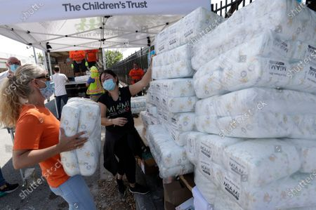 Rachel Spector, left, with The Children's Trust, and Adrienna Sotomayor, center, Miami Diaper Bank Program Coordinator, stack diapers at Curley's House of Style, Inc., food bank, in Miami. Curley's House of Style, along with The Children's Trust and the Miami Diaper Bank, distributed diapers and baby items to families financially impacted by the coronavirus pandemic