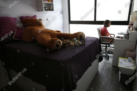 Raquel Rodriguez, 11, attends virtual classes from her room in an apartment in Mexico City, . Raquel along with her brother Andres, father Bernardo Rodriquez and mother Patricia Fernandez have self-quarantined for the last three weeks to protect themselves against the spread of the new coronavirus