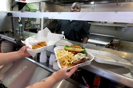Stock Image of Carry out lunches are served up by head chef Andre James at Chase's Diner, in Chandler, Ariz. Owner Skip Chase has maintained all his employees and raised their hourly pay to compensate for lost tips since his business has gone to carry-out only in compliance with Arizona's COVID-19, Coronavirus mandates. Chase's has lost over $20,000 since closing their in-house seating area in March and Chase has spent over $9,000 in personal money to supplement his staff's payroll in an effort to remain open