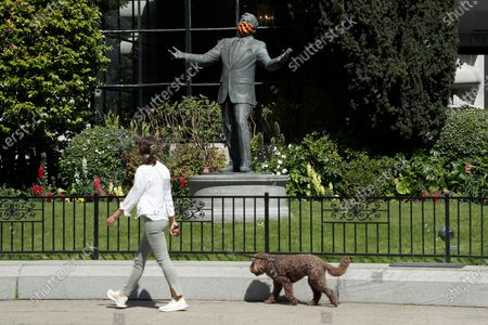 A person and her dog walk past a Tony Bennett statue with a protective mask covering on the lawn of the historic Fairmont Hotel in San Francisco, California, USA, 23 April 2020. Tony Bennett invites people to virtual sing-along of 'I Left My Heart in San Francisco' on 25 April. The event takes a moment to celebrate frontline heatlh workers and everyone working to make a difference during the COVID-19 pandemic. Bennett's very first performance of 'I Left My Heart in San Francisco' took place inside the Fairmont Hotel in December 1961.