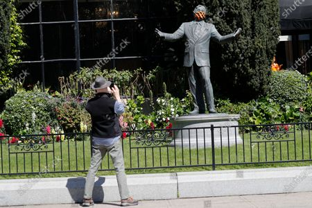 A passerby stops to take picture of a Tony Bennett statue with a protective mask covering on the lawn of the historic Fairmont Hotel in San Francisco, California, USA, 23 April 2020. Tony Bennett invites people to virtual sing-along of 'I Left My Heart in San Francisco' on 25 April. The event takes a moment to celebrate frontline heatlh workers and everyone working to make a difference during the COVID-19 pandemic. Bennett's very first performance of 'I Left My Heart in San Francisco' took place inside the Fairmont Hotel in December 1961.
