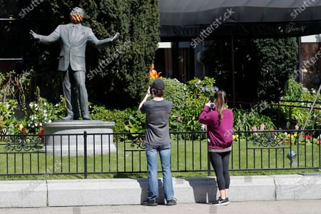 A couple stop to take pictures of a Tony Bennett statue with a protective mask covering on the lawn of the historic Fairmont Hotel in San Francisco, California, USA, 23 April 2020. Tony Bennett invites people to virtual sing-along of 'I Left My Heart in San Francisco' on 25 April. The event takes a moment to celebrate frontline heatlh workers and everyone working to make a difference during the COVID-19 pandemic. Bennett's very first performance of 'I Left My Heart in San Francisco' took place inside the Fairmont Hotel in December 1961.
