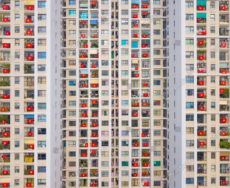 Stock Picture of Local residents in a block of flats expressing compassion and solidarity as they hang the national flag of Vietnam from their balconies during the coronavirus pandemic
