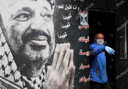 Palestinian man wearing gloves and mask to help curb the spread of the coronavirus stands next to a portrait of late Palestinian leader Yasser Arafat, at Jalil, or Galilee Palestinian refugee camp, in Baalbek, Lebanon, . Authorities closed all entrances to a Palestinian refugee camp in eastern Lebanon Friday after four more people tested positive for the coronavirus, heightening concerns over the virus spreading among the population of overcrowded refugee camps and settlements