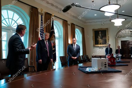 Stock Image of President Donald Trump listens during a demonstration of ways NASA is helping to combat the coronavirus, in the Cabinet Room of the White House, in Washington. From left, Dave Gallagher, Associate Director, NASA Jet Propulsion Laboratory, Trump, and Dave Gallagher, Associate Director, and NASA administrator Jim Bridenstine