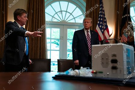 Associate director of the NASA jet propulsion laboratory Dave Gallagher shows President Donald Trump a ventilator created by their engineers during a demonstration in the Cabinet Room of the White House, in Washington