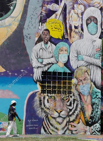 """Man walks past a mural featuring various healthcare workers wearing personal protective equipment and television show personality from """"Tiger King,"""" Joe Exotic wearing a face mask, in Miami. Muralist Kyle Holbrook originally painted Exotic without a mask but later changed it to include the mask and added the healthcare workers to honor their work. Miami-Dade County continues to be the state's coronavirus epicenter with a third of the state's confirmed cases"""