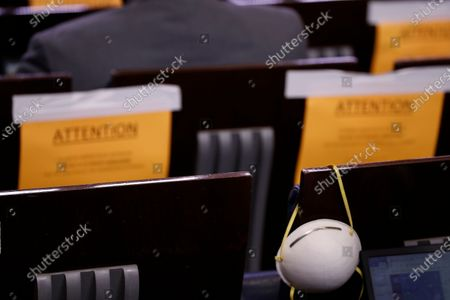 """A face mask hangs on a chair as President Donald Trump speaks about the coronavirus in the James Brady Press Briefing Room of the White House in Washington. On Friday, April 24, 2020, The Associated Press reported on a video circulating online incorrectly asserting comments between Fox News and New York Times journalists reveal they believe COVID-19 was a """"hoax."""" The video feed that was actively recording the White House briefing room on Monday, April 20, captured an exchange between Fox News chief White House correspondent John Roberts and New York Times photographer Doug Mills, saying COVID-19 was a """"hoax"""" and """"we've all been vaccinated,"""" but the comments were taken out of context. Roberts told the AP the comments were made in jest. Mills told the AP in an email that there is no vaccine, and the conversation was a """"total joke"""