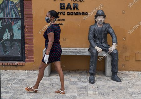 Stock Image of A woman wearing a mask walks in front of a statue of famous Spanish musician Joaquin Sabina, in Santo Domingo, Dominican Republic, 24 April 2020. Countries around the world are taking increased measures to stem the spread of the SARS-CoV-2 coronavirus which causes the Covid-19 disease.