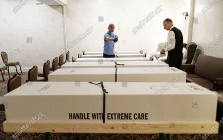 Funeral directors Omar Rodriguez (L) and Nicholas Cassese (R) double check the paperwork on some of the bodies the home is handling, either for burial or cremation, at the Gerald J. Neufeld Funeral Home in the Elmhurst neighborhood of Queens, New York, USA, 24 April 2020. Rodriguez and Cassese, who run their own funeral services businesses, have been helping at the Neufeld Funeral home since March, as it is has been overwhelmed with the number of families needing funeral services in the area as a result of the coronavirus pandemic, which has specifically affected this neighborhood. Many funeral homes in the area have closed for safety reasons, leaving a limited number of options for people trying to manage the large number of people who have died, many from COVID-19.