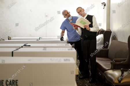 Funeral directors Omar Rodriguez (L) and Nicholas Cassese (R) double check the paperwork on some of the bodies the home is handling, either for burial or cremation, at the Gerald J. Neufeld Funeral Home in the Elmhurst neighborhood of Queens, New York, USA, 24 April 2020. Neufeld who runs the family owned and operated funeral home that his father started in 1940, has been overwhelmed with the number of families need funeral services in the area as a result of the coronavirus pandemic, which has specifically affected this neighborhood, which is where Joe grew up. Many funeral homes in the area have closed for safety reasons, leaving a limited number of options for people trying to manage the large number of people who have died, many from COVID-19.