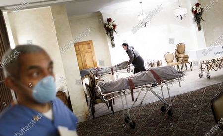 Funeral director Joe Nuefeld Jr. (R) transfers one of the many bodies the home is handling, either for burial or cremation, with funeral director Omar Rodriguez (L) in the foreground, at the Gerald J. Neufeld Funeral Home in the Elmhurst neighborhood of Queens, New York, USA, 24 April 2020. Rodriguez, who runs his own funeral services business, has been helping Neufeld and his father, Joe Sr., with the overwhelming number of families needing funeral services in the area as a result of the coronavirus pandemic, which has specifically affected this neighborhood, which is where Joe grew up. Many funeral homes in the area have closed for safety reasons, leaving a limited number of options for people trying to manage the large number of people who have died, many from COVID-19.