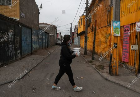 Natalia Sanchez, wearing a protective face mask, crosses a street with plates of food that she is delivering to fellow neighbors who are facing hardship because of lost income due to the new coronavirus pandemic, in El Nocedal on the outskirts of Santiago, Chile
