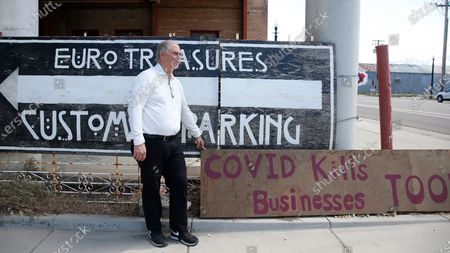 """Euro Treasures Antiques owner Scott Evans stands next to a """"covid kills businesses too"""" sign outside of his store, in Salt Lake City. Evans is closing his art and antique store after 40 years. This year started out well for his business, then COVID-19 hit, along with shelter-in-place orders. With a drastic drop in customers, Evans says it was no longer cost effective to stay open"""