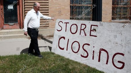 Euro Treasures Antiques owner Scott Evans stands next to the store closing sign outside of his business, in Salt Lake City. Evans is closing his art and antique store after 40 years. Evans, made the tough decision to close down for good. This year started out well for his business, then COVID-19 hit, along with shelter-in-place orders. With a drastic drop in customers, Evans says it was no longer cost effective to stay open