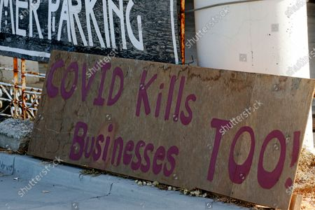 """Covid kills businesses too"""" sign is shown outside Euro Treasures Antiques, in Salt Lake City. Scott Evans is closing his art and antique store after 40 years. This year started out well for his business, then COVID-19 hit, along with shelter-in-place orders. With a drastic drop in customers, Evans says it was no longer cost effective to stay open"""