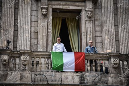 Milan mayor Giuseppe 'Beppe' Sala (L) and Italian musician Saturnino (Saturnino Celani) sing the popular protest folk song 'Bella ciao' from the balcony of Palazzo Marino (Milan's city hall) over Piazza San Fedele, in the center of Milan, northern Italy, 25 April 2020, on the occasion of the country's 75th Liberation Day, which marks the end of fascist rule in Italy during World War II (WWII). Italians will not be able to step out and celebrate the 75th anniversary of Liberation Day due to the nationwide lockdown to prevent the spread of the coronavirus disease (COVID-19) pandemic.