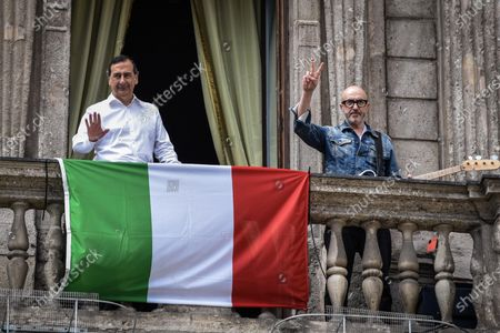Milan mayor Giuseppe 'Beppe' Sala (L) and Italian musician Saturnino (Saturnino Celani) gesture prior to singing the popular protest folk song 'Bella ciao' from the balcony of Palazzo Marino (Milan's city hall) over Piazza San Fedele, in the center of Milan, northern Italy, 25 April 2020, on the occasion of the country's 75th Liberation Day, which marks the end of fascist rule in Italy during World War II (WWII). Italians will not be able to step out and celebrate the 75th anniversary of Liberation Day due to the nationwide lockdown to prevent the spread of the coronavirus disease (COVID-19) pandemic.