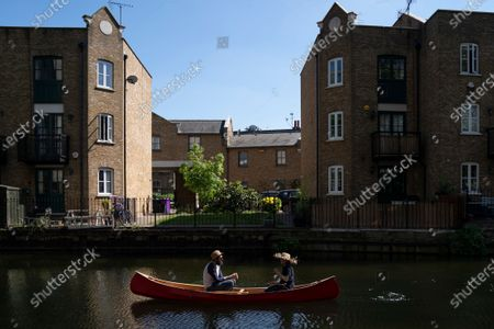 Members of the public use a boat to travel down a canal next to Victoria Park in London, Britain, 25 April, 2020. Britons are now in their fifth week of lockdown due to the Coronavirus pandemic. Countries around the world are taking increased measures to stem the widespread of the SARS-CoV-2 coronavirus which causes the Covid-19 disease.