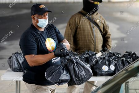 "Stock Photo of Baltimore Mayor Bernard ""Jack"" Young wears a mask to protect from the coronavirus as he prepares to deliver bags of food to a vehicle during a donation drive by World Central Kitchen in the parking lot of the Camden Yards Sports Complex, in Baltimore. World Central Kitchen conducted its food relief operation during the coronavirus pandemic to help relieve food insecurity faced by Baltimore's vulnerable communities, at the request of Governor Larry Hogan"
