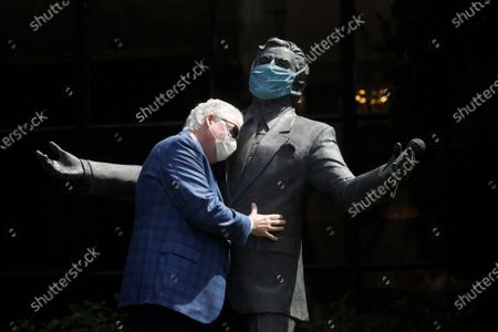 """Paul Tormey, Regional Vice President of Fairmont Hotels, wears a mask while hugging a statue of singer Tony Bennett outside of the Fairmont San Francisco hotel before leading hotel workers in a singing of the song """"I Left My Heart in San Francisco,"""", in San Francisco. Bennett had encouraged San Franciscans to join him in a sing-a-long from their homes during shelter in place orders for COVID-19 concerns"""
