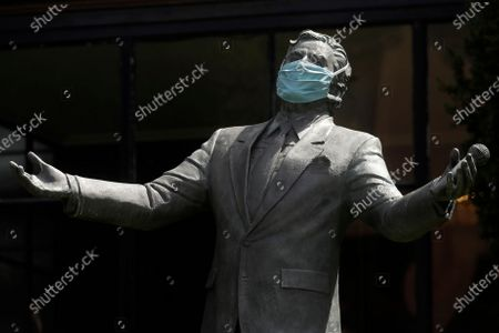 """Face mask is placed over the face of the statue of singer Tony Bennett outside the Fairmont San Francisco hotel before hotel workers sang """"I Left My Heart in San Francisco,"""", in San Francisco. Bennett had encouraged San Franciscans to join him in a sing-along from their homes during shelter-in-place orders due to COVID-19 concerns"""