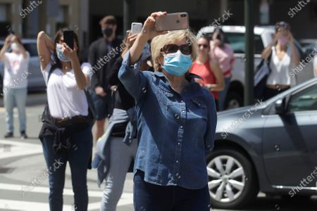 """Fairmont San Francisco hotel workers and pedestrians wear masks while maintaining distance during a singing of the Tony Bennett song """"I Left My Heart in San Francisco,"""" outside of the hotel, in San Francisco. Bennett had encouraged San Franciscans to join him in a sing-a-long from their homes during shelter in place orders for COVID-19 concerns"""