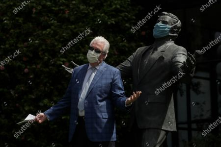 """Paul Tormey, Regional Vice President of Fairmont Hotels, wears a mask while gesturing in front of a statue of singer Tony Bennett outside of the Fairmont San Francisco hotel before leading hotel workers in a singing of the song """"I Left My Heart in San Francisco,"""", in San Francisco. Bennett had encouraged San Franciscans to join him in a sing-a-long from their homes during shelter in place orders for COVID-19 concerns"""