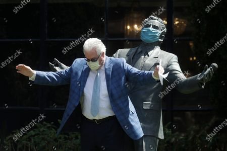 """Paul Tormey, Regional Vice President of Fairmont Hotels, wears a mask while gesturing in front of a statue of singer Tony Bennett outside of the Fairmont San Francisco hotel after leading hotel workers in a singing of the song """"I Left My Heart in San Francisco,"""", in San Francisco. Bennett had encouraged San Franciscans to join him in a sing-a-long from their homes during shelter in place orders for COVID-19 concerns"""